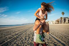Young man carrying girlfriend on shoulders on San Diego beach Kuvituskuvat