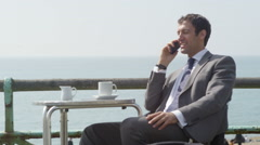 4k Businessman talking on mobile phone and drinking coffee at seafront cafe Stock Footage