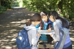 Three young female hikers looking at map Stock Photos