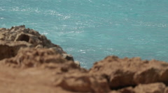 Coastline ocean wave splash in rocky island, close up of idyllic island by sunny Stock Footage