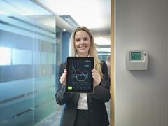 Portrait of office worker holding digital tablet next to office thermostat Kuvituskuvat