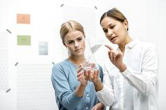 Female colleagues discussing workings of the hourglass Stock Photos