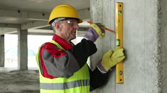 Worker with yellow level at building site Stock Footage