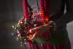 Close up of young woman holding tangle of christmas lights Stock Photos