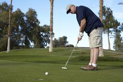 Portrait of mature male golfer taking shot on green - stock photo
