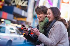 Young couple competing on cell phones, New York City, USA Stock Photos