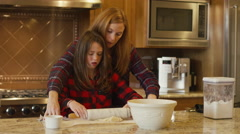 A mother helps her daughter roll dough with a rolling pin Stock Footage