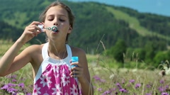 Girl blowing soap bubbles Stock Footage