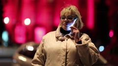 Senior woman with cell phone stands near the road and red building in nighttime Stock Footage