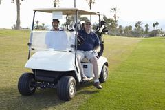 Portrait of two male golfers in golf buggy - stock photo