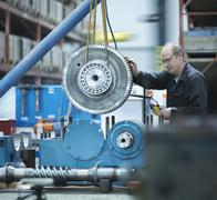 Engineer assembling industrial gearbox in engineering factory Stock Photos