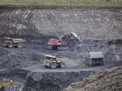 Diggers and dumper trucks at work in surface coal mine - stock photo