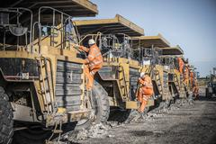 Dumper truck drivers climb down for break at surface coal mine Stock Photos