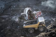 Excavator and dumper truck in void at surface coal mine - stock photo