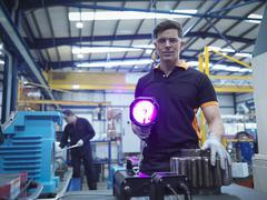 Engineer using ultraviolet light to test for cracks in gear wheel, portrait Stock Photos