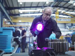 Engineer using ultraviolet light to test for cracks in gear wheel Stock Photos