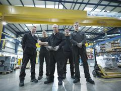 Group of engineers and apprentices in engineering factory, portrait Stock Photos