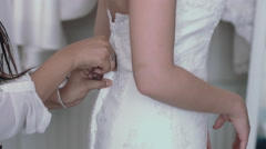Young entrepreneur helping bride with dress fitting Stock Footage
