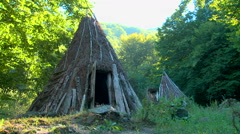 Traditional old cottage made of straw and sticks in the forest Stock Footage