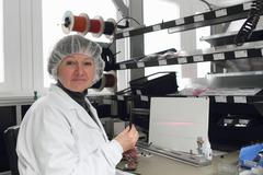 Female scientist testing lasers in laboratory Kuvituskuvat