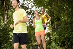 Small group of runners training in woods Stock Photos