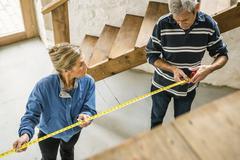 Senior couple doing DIY, using measuring tape Stock Photos