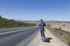 Hitchhiker on side of road Stock Photos