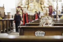 Portrait of female toddler peeking over church pew Stock Photos