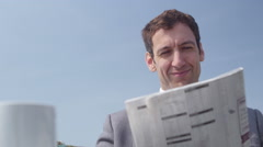 4k Businessman reading newspaper and drinking coffee at outdoor cafe Stock Footage