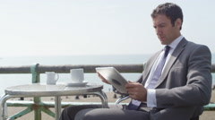 4k Businessman using computer tablet and drinking coffee at seafront cafe Stock Footage