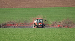 Old red Tractor spraying field, rural landscape in countryside - stock footage
