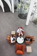 Overhead view of business meeting in office atrium - stock photo