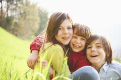 Sister and younger brothers sitting in grassy field - stock photo