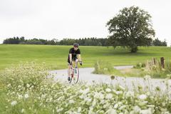 Mature male cyclist on country road Stock Photos