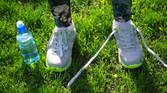 girl stopped running to tie the laces on running shoes. fitness girl training - stock footage