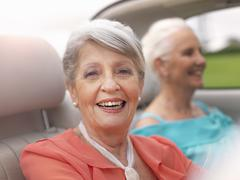 Two senior women driving in convertible Stock Photos