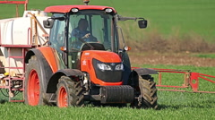 Old red Tractor spraying field, rural landscape in countryside Stock Footage