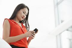 Young businesswoman reading texts on cellphone Stock Photos