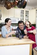 Mature couple in kitchen laughing with young daughter Stock Photos