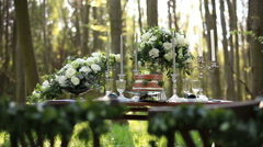 Beautiful wedding decorated table setted for two on nature in the forest Stock Footage