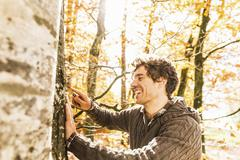 Man carving into tree trunk with penknife Stock Photos
