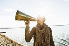 Young woman using megaphone by lake Stock Photos