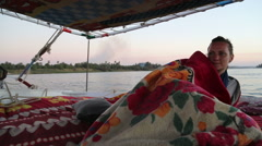 Female tourist covered with blanket on felucca at sunset Stock Footage