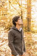Portrait of man wearing cardigan in forest looking up Stock Photos