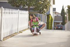 Siblings cycling on driveway - stock photo