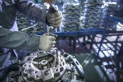 Close up of engineer assembling industrial clutch on production line Stock Photos