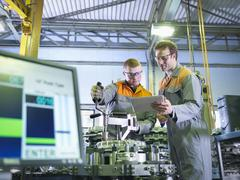 Engineer and apprentice using digital tablet at work station in factory Stock Photos