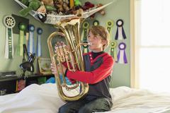 Boy playing tuba in bedroom Kuvituskuvat