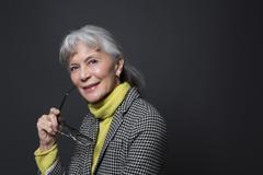 Studio portrait of wise senior woman holding spectacles - stock photo