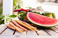 Still life of homegrown watermelon and carrots - stock photo
